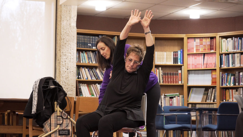 person with MS practicing yoga in a chair with assistance
